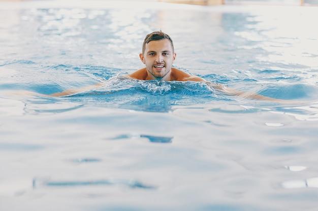 Um homem bonito flutuando em uma grande piscina em casa