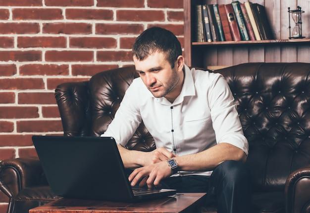 Um homem bonito lê informações no laptop no fundo de uma prateleira com livros.