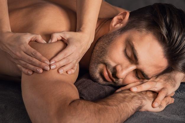 Um homem bonito recebendo uma massagem nas costas deitado no spa. mão de uma mulher fazendo sinal coração conceito de amor