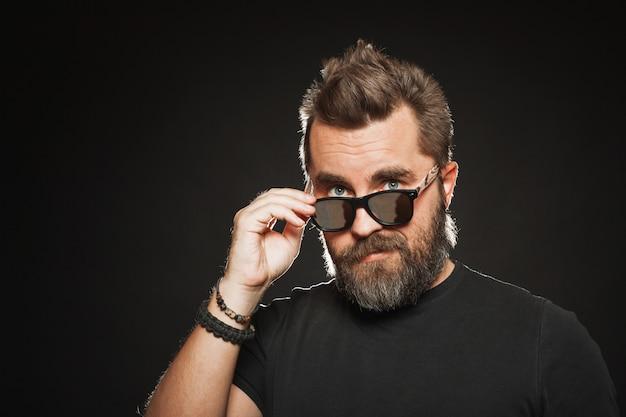 Um homem bonito usa óculos escuros e sorrisos.