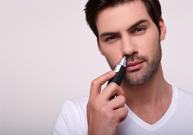 Um homem bonito usa um aparador de nariz.