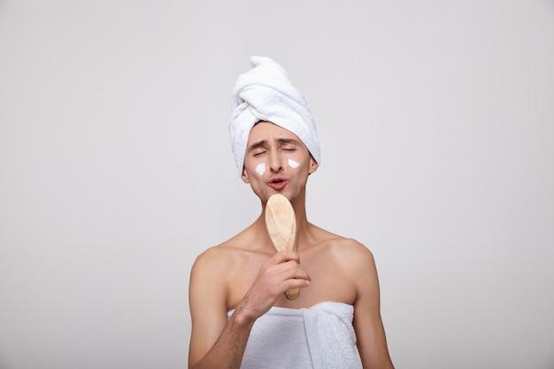 Um homem branco canta em um pente como um microfone depois do banho.
