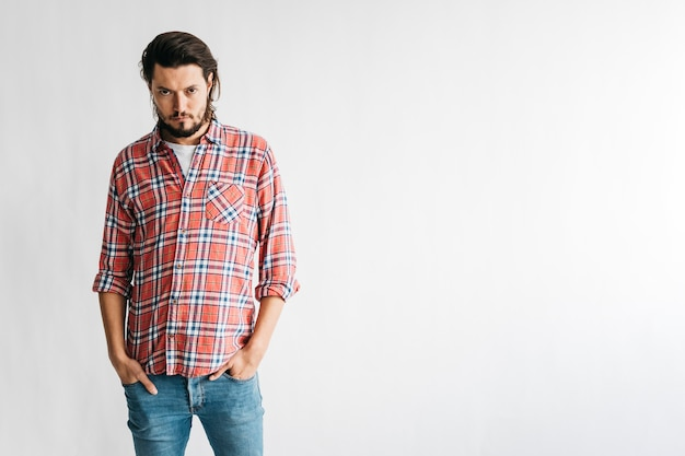 Um homem bravo de camisa quadriculada com as duas mãos no bolso isolado no fundo branco