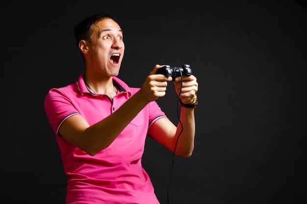 Um homem brinca com um joystick em casa em um fundo preto