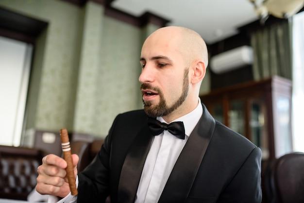 Um homem brutal com um casaco formal fuma um charuto.