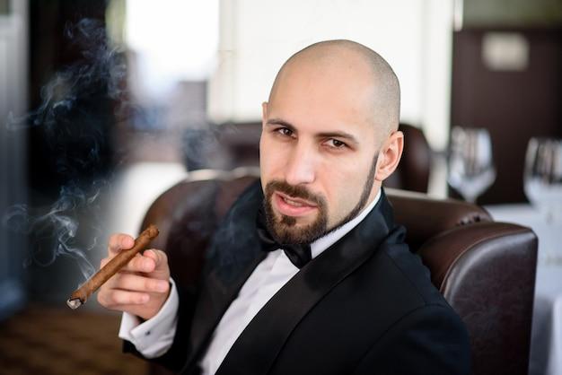 Um homem brutal de casaco fuma um charuto.