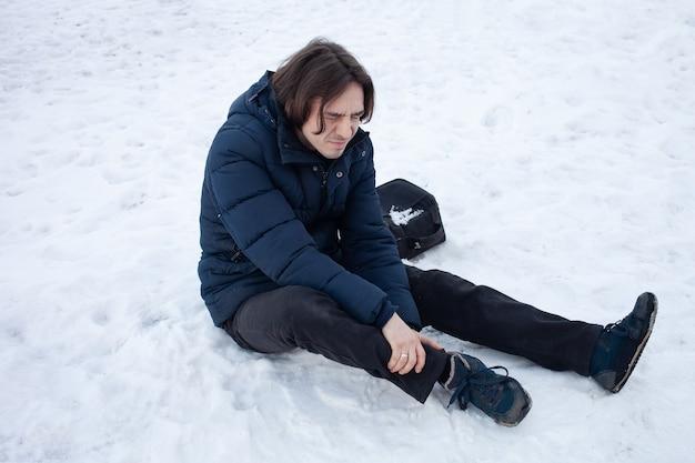 Um homem cai na neve. o homem escorregou e ficou ferido