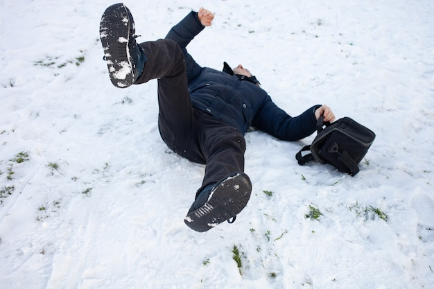 Um homem cai na neve. o homem escorregou e ficou ferido Foto Premium