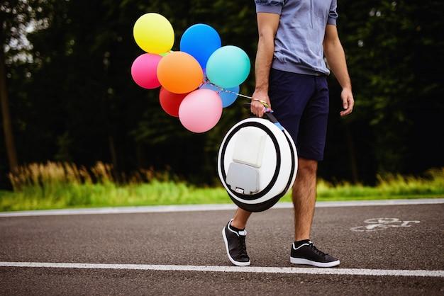 Um homem caminha ao longo do caminho do parque com um monoclean.