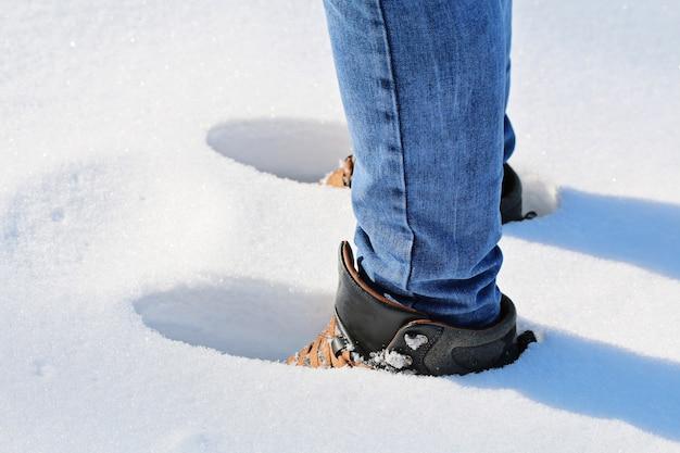 Um homem caminha na neve, pegadas na neve, neve profunda, monte de neve.