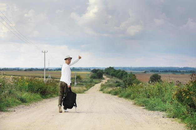 Um homem caminha por uma estrada secundária. carona em todo o país. um homem para um carro que passa na estrada.