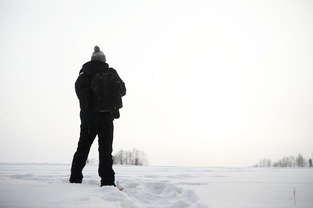 Um homem caminhando. paisagem de inverno. turista na jornada de inverno.