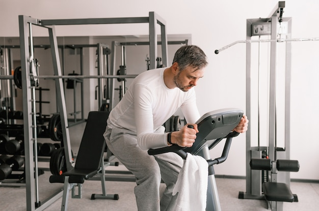 Um homem cansado de camiseta branca realiza exercícios em uma bicicleta ergométrica. treinamento cardíaco.