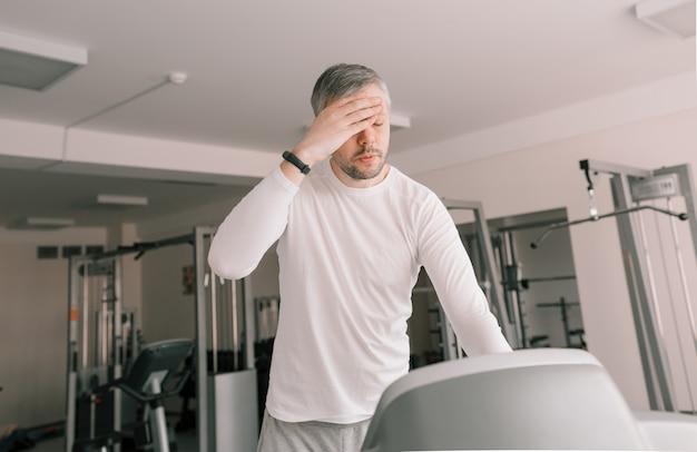 Um homem cansado em uma esteira limpa o suor do rosto com a mão. sessão de treinamento cardiovascular intensivo.