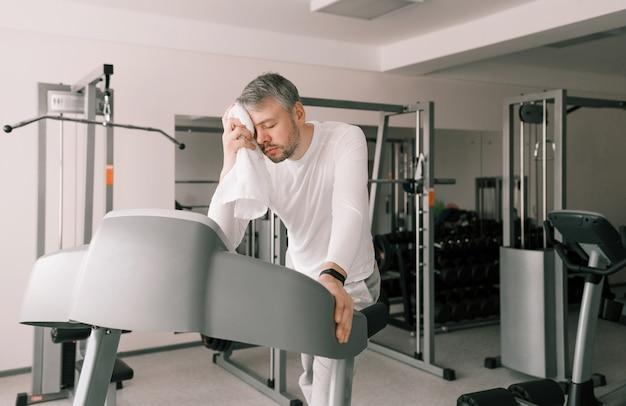 Um homem cansado em uma esteira limpa o suor do rosto com uma toalha. treinamento cardiovascular de estilo de vida saudável. cuidados com o corpo