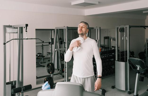 Um homem cansado enxuga o suor do rosto com uma toalha depois de fazer exercícios em uma esteira. treino cardio