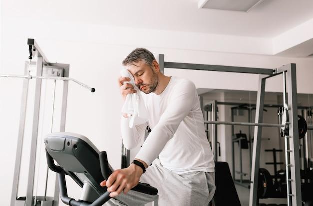 Um homem cansado enxuga o suor do rosto com uma toalha durante um exercício em uma bicicleta ergométrica. treino cardio