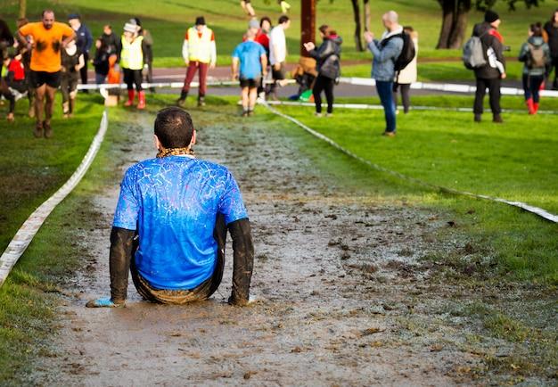 Um homem cansado exausto depois de uma atividade de exercício extremo, em uma corrida de lama