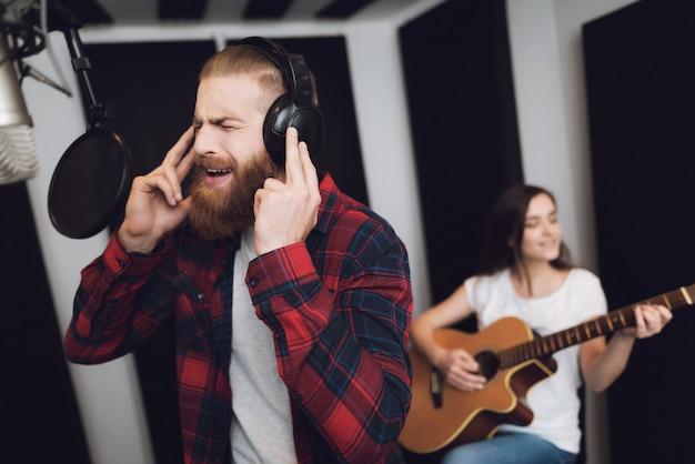 Um homem canta e uma mulher toca violão.