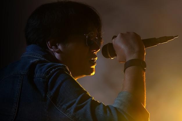 Um, homem, cantando, em, um, microfone, sob, holofote, com, fumaça, ligado, um, fase