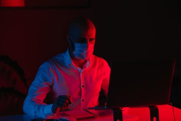 Um homem careca com uma máscara facial médica está trabalhando remotamente em um laptop em casa