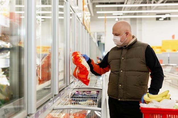 Um homem careca com uma máscara médica e luvas em um supermercado escolhe produtos. pandemia do coronavírus.