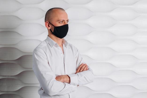 Um homem careca de camisa branca e máscara preta