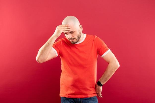 Um homem careca de meia-idade, com barba e uma camiseta vermelha. segura sua cabeça com as mãos. ele está com uma dor de cabeça.
