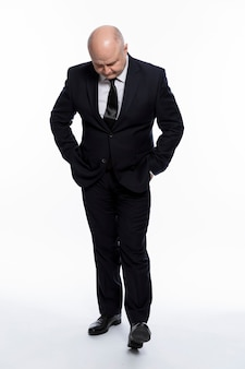 Um homem careca de meia-idade em um terno preto rígido se levanta e olha para baixo, com as mãos nos bolsos. complexidades de negócios. altura toda. fundo branco. vertical.