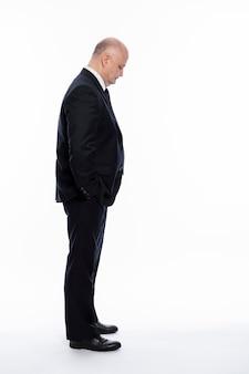 Um homem careca de meia-idade em um terno preto rígido se levanta e olha para baixo, com as mãos nos bolsos. complexidades de negócios. vista lateral. altura toda. fundo branco. vertical.