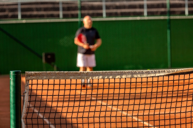 Um homem careca de meia-idade joga tênis na quadra ao ar livre. dia ensolarado. borrão.
