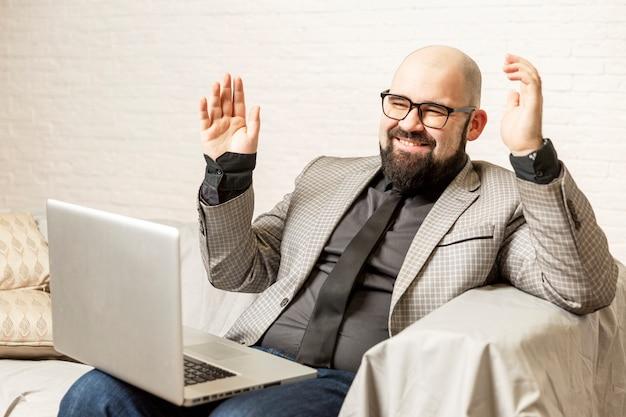 Um homem careca de óculos se senta em um sofá e usa um laptop. blogging e treinamento.