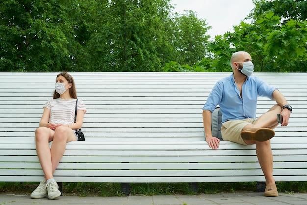 Um homem careca e uma jovem sentada em extremos opostos do banco, mantendo distância um do outro para evitar a propagação do coronavírus.
