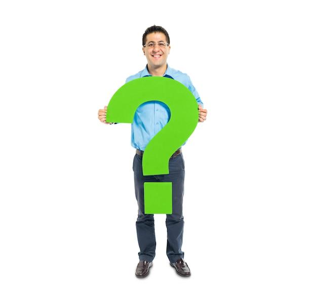 Um homem casual inteligente segurando um ponto de interrogação verde