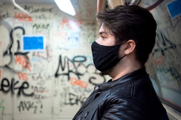 Um homem caucasiano com barba e máscara médica preta no metrô com o interior pintado