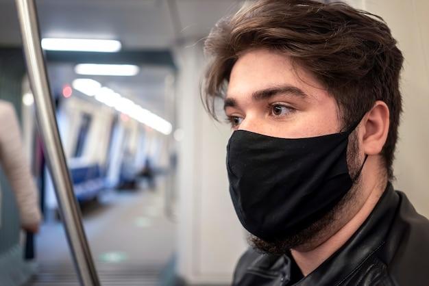 Um homem caucasiano com barba e máscara médica preta no metrô