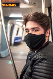 Um homem caucasiano com barba e máscara médica preta, olhando para a câmera no metrô em bucareste, romênia