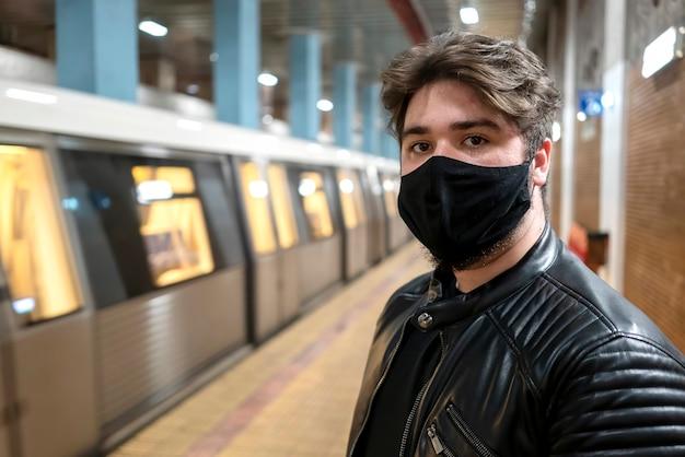 Um homem caucasiano com barba e máscara médica preta olhando para a câmera no metrô
