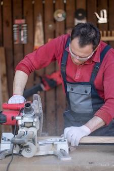 Um homem caucasiano com macacão de proteção e óculos corta uma prancha de carvalho com uma serra circular