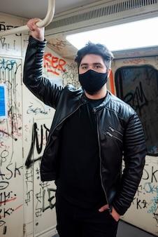 Um homem caucasiano com máscara médica preta permanecendo e segurando o corrimão no metrô com o interior pintado
