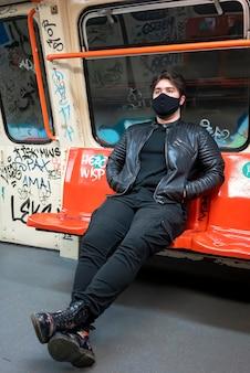 Um homem caucasiano com máscara médica preta sentado em uma cadeira no metrô com o interior pintado