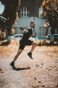 Um homem caucasiano, exercitando a suspensão treinamento trx no parque.