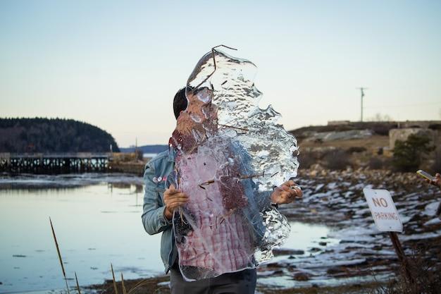 Um homem caucasiano, segurando um pedaço gigantesco de gelo nas mãos com um lago no fundo