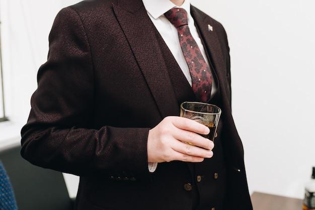 Um homem caucasiano, vestindo um terno e segurando um copo