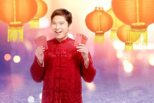 Um homem chinês asiático em um vestido cheongsam segurando envelopes vermelhos
