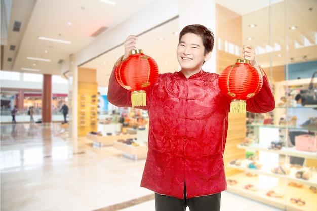 Um homem chinês asiático em um vestido cheongsam segurando lanterna chinesa