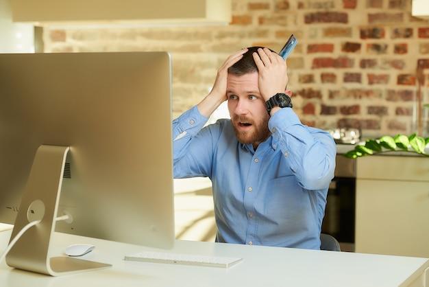 Um homem chocado com os preços de uma loja on-line e colocando as mãos com um cartão na cabeça na frente do computador