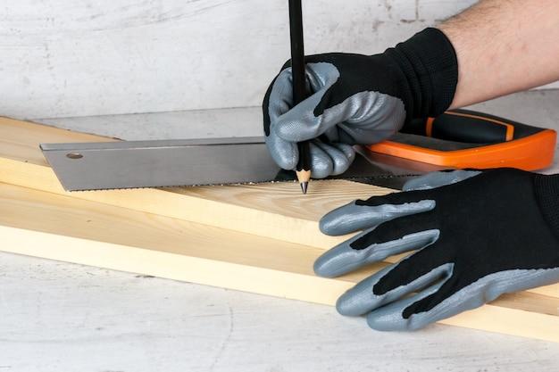 Um homem coloca marcas nas barras de madeira com um lápis para continuar a trabalhar com uma serra. diy em casa conceito
