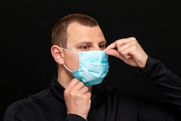 Um homem coloca uma máscara médica no rosto, instruções sobre como usar uma máscara
