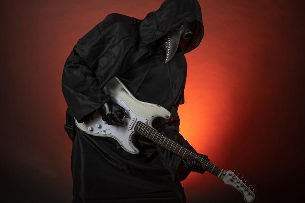 Um homem com a fantasia de médico da peste toca violão emocionalmente em um fundo vermelho